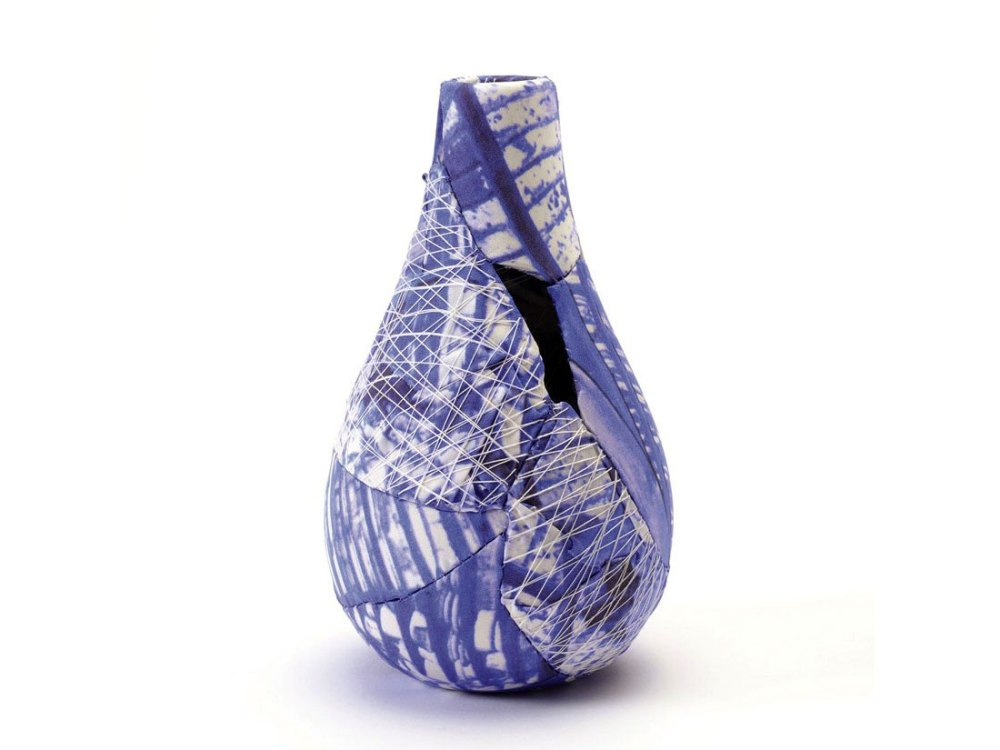 A small vase: broken pieces are covered in decorative fabric and stitched back together in the original shape.