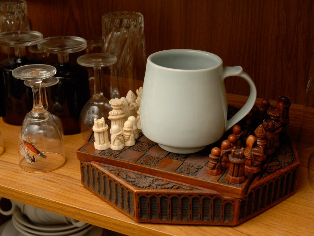 A white simple mug sits on an intricately carved chess board.