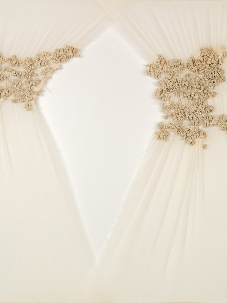 Sheets of cream material delicately draped, with cream coloured thread embroidered on to the surface.