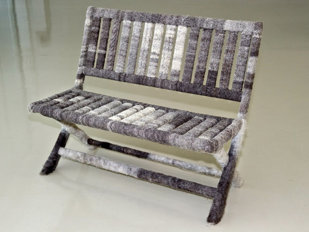 A bench covered in hand knitted grey and white woollen pieces.