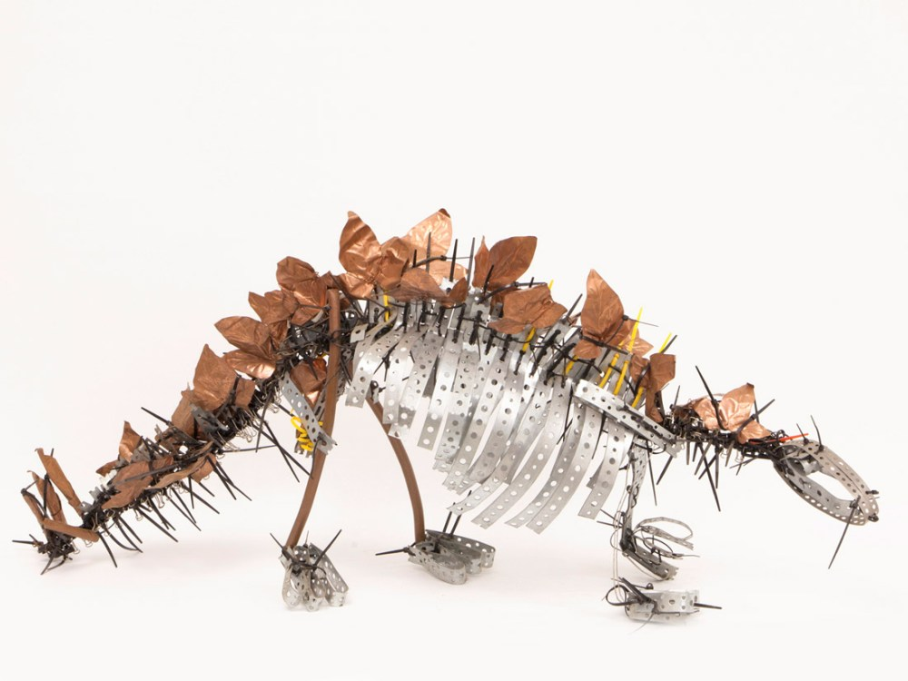 A dinosaur figurine made from found materials, off cuts and scraps of metal and plastic.
