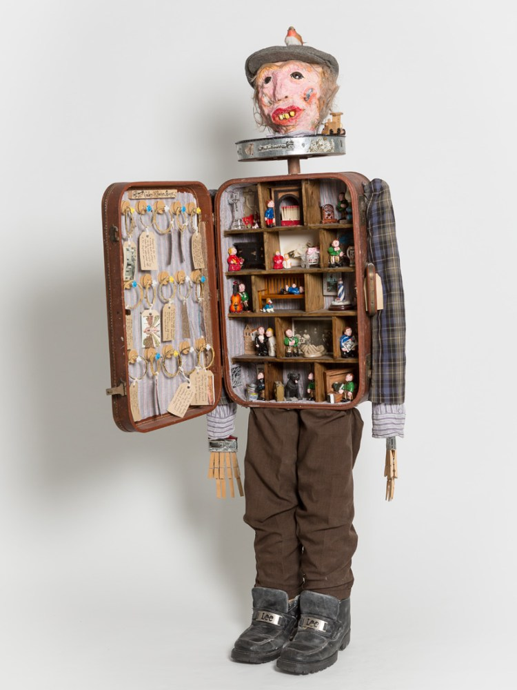 A figure made from found objects including pegs and a briefcase. The briefcase is open showing various figurines in differing settings.