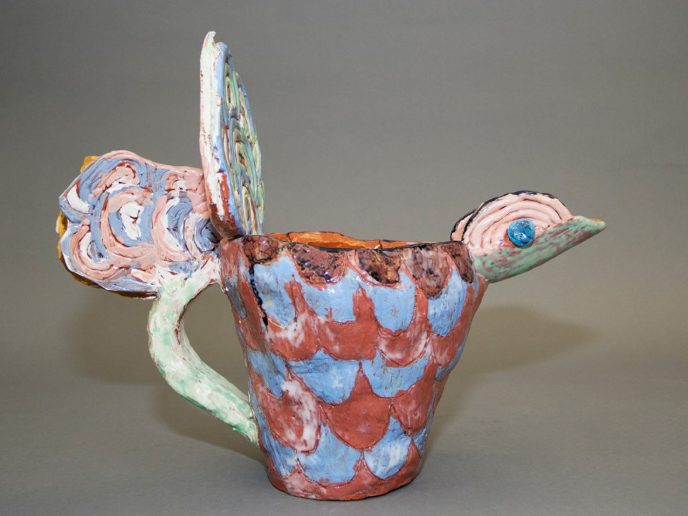 A colourful ceramic jug built to look like a bird.