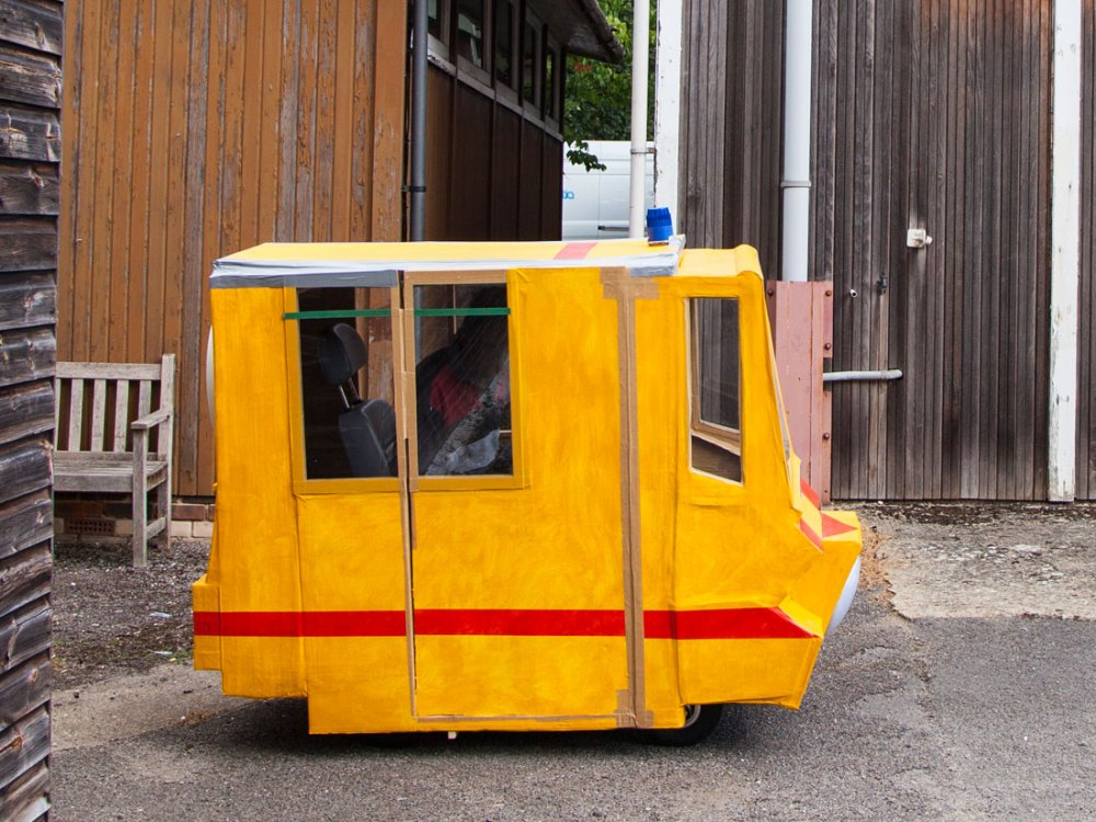 A small vehicle is crudely made from cardboard and painted bright orange.