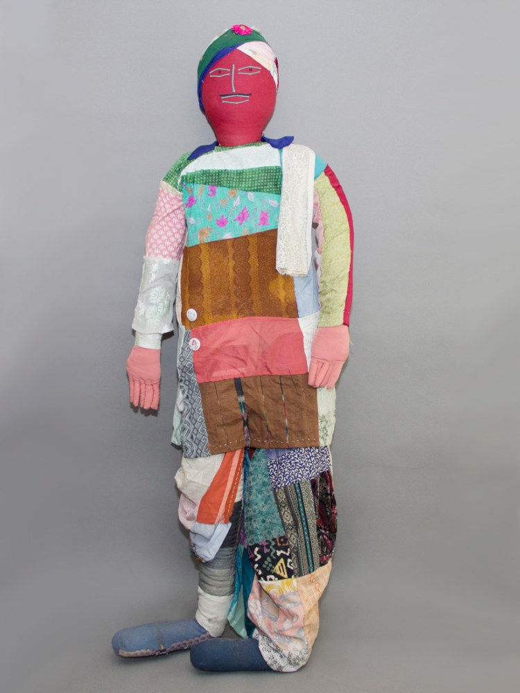 A 3D figure made from various pieces of cloth stands before a grey background.