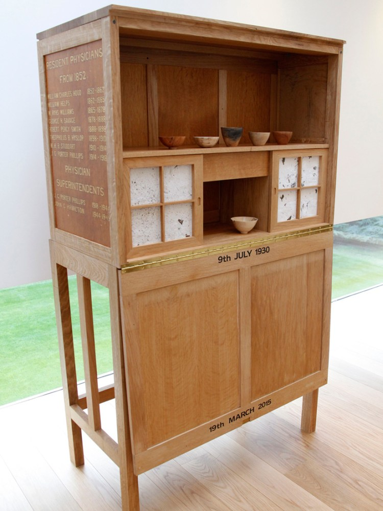 wooden cabinet with small wooden bowls on a shelf and text