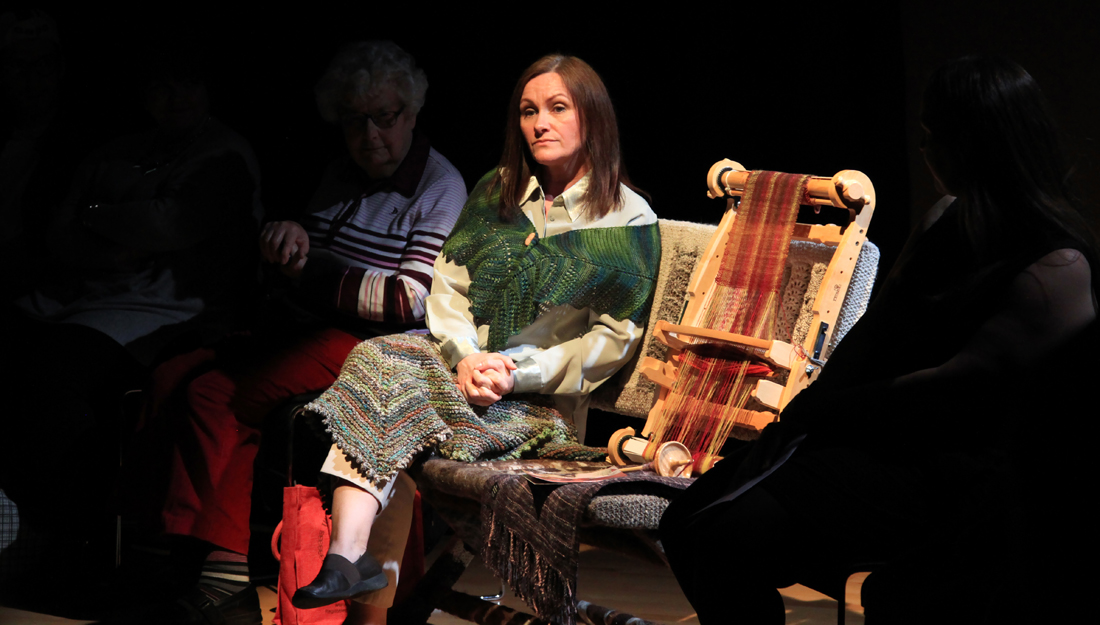 A woman sits on a bench, lit by a spotlight. A small loom next to her. She looks deep in thought.