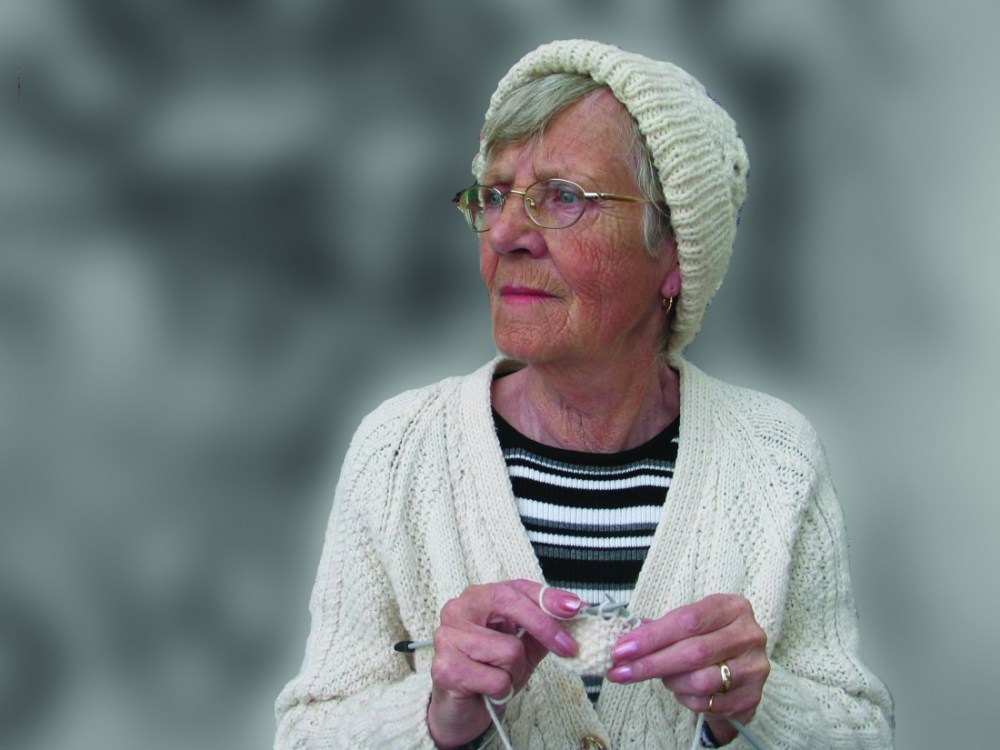 older lady wearing knitted hat and cardigan is knitting