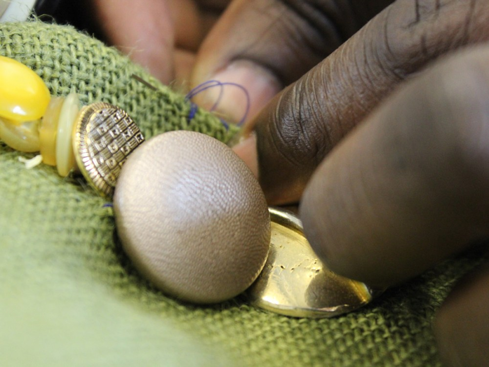 A close up of Andrew's hands sewing a variety of gold buttons on green fabric