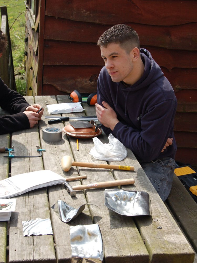 A man sits at a bench with various tools and materials infront of him including a hammer and sheet metal.