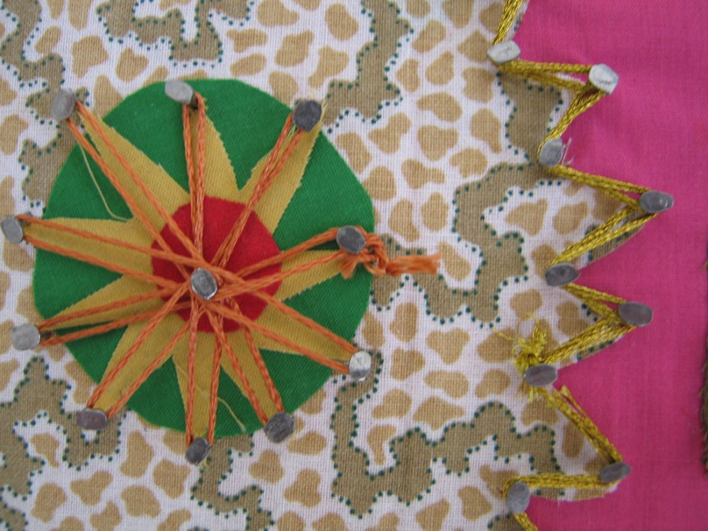 A close up detail of pins on brightly coloured fabric with thread woven around them.