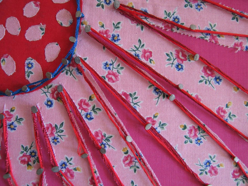 A close up detail of pins on floral brightly coloured fabric with thread woven around them.