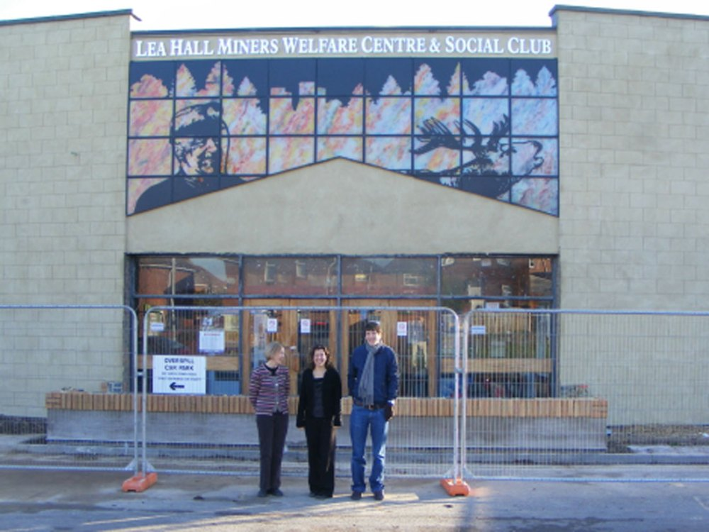 A man and two women stand infront of Lea Hall Miners Welfare Centre and Social Club.