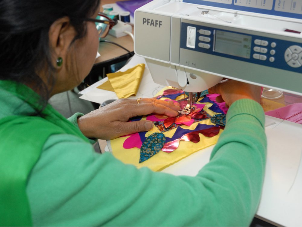 A woman stitches her colourful flower design on to yellow fabric using a sewing machine.