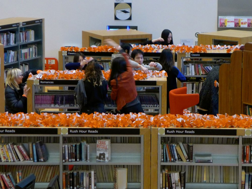 People in a library reach above the top shelf to pick up the origami shapes made from orange and white paper.