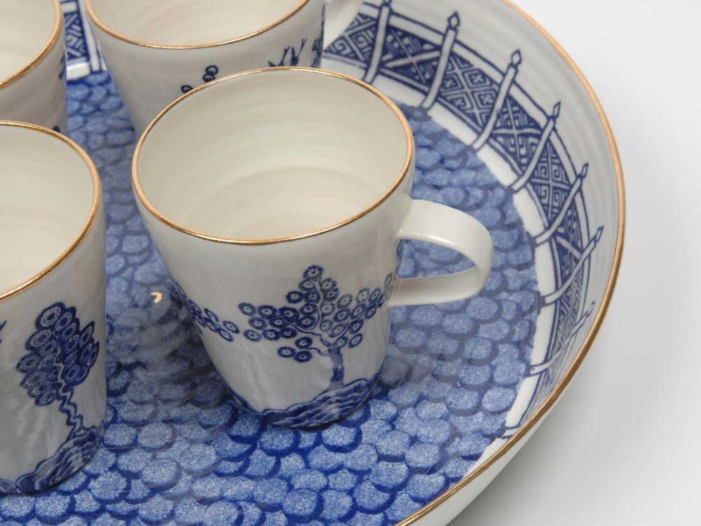 a blue and white teacup with a gold rim sits on top of a bowl which is blue and white with a gold rim.