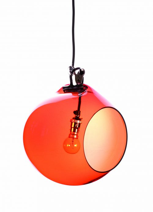 A orange sphere shapes light with a circle shaped hole cut out at the front hangs from the ceiling with a light bulb inside.