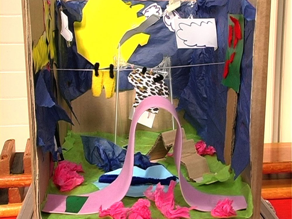 A scene created in a cardboard box using various materials including tissue paper and string.