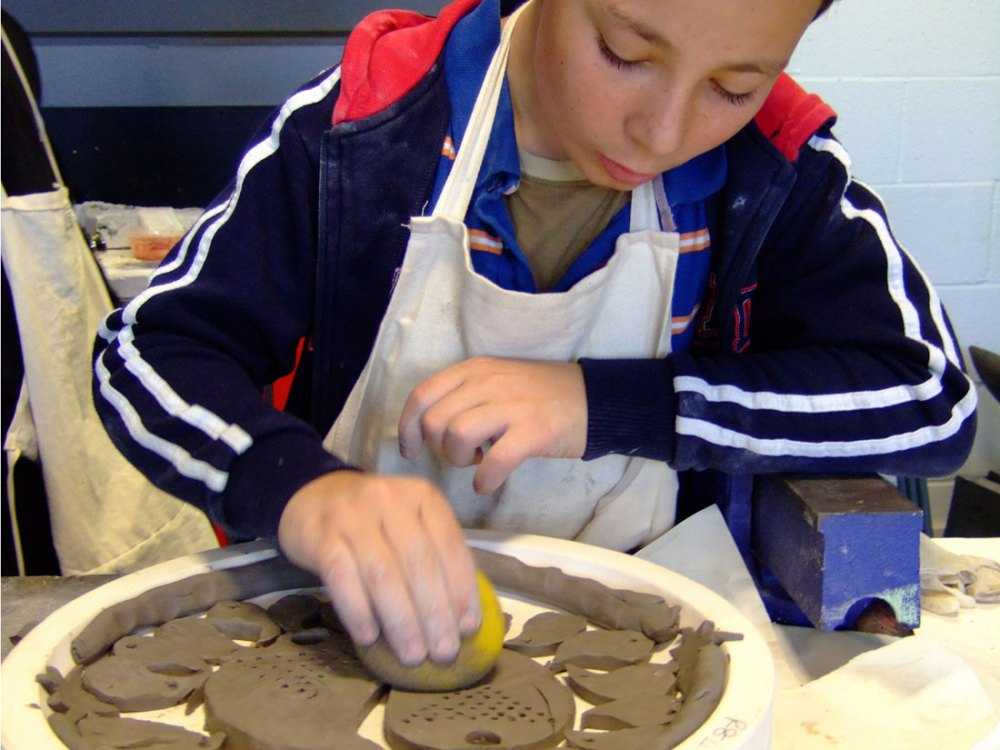 A young boy cleans up the side of the clay using a sponge.
