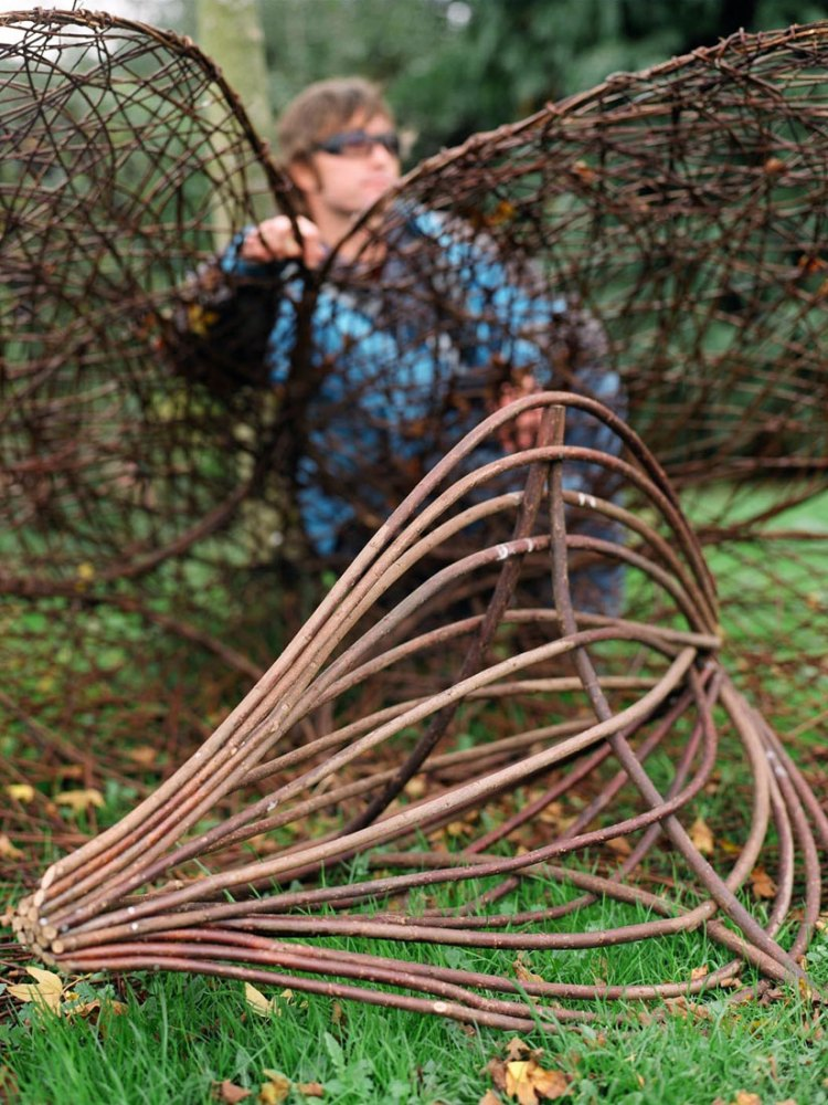 Various intricate willow sculptures are at the foreground, with the artist sat behind them.