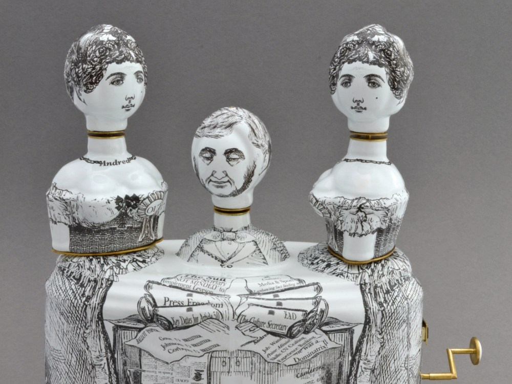 A satirical ceramic sculpture featuring 3 figures with black line drawing markings.