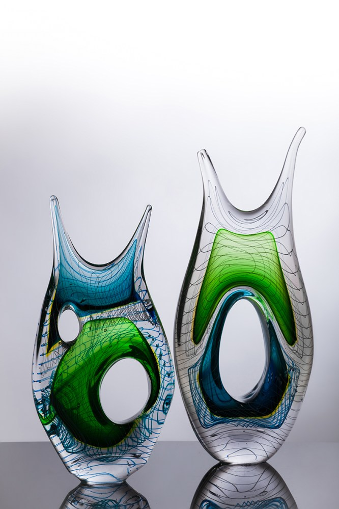 2 glass sculptures: they are organic shaped with bright sections and a linear pattern.