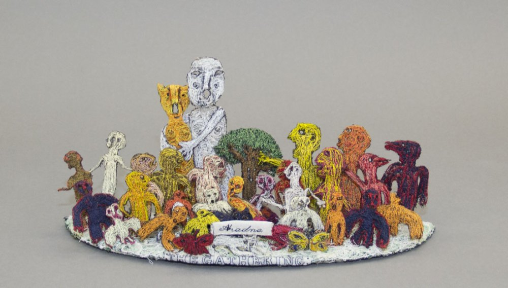 Various figures made from textile and yarn surround a textile tree with the words 'The Gathering' at the front.
