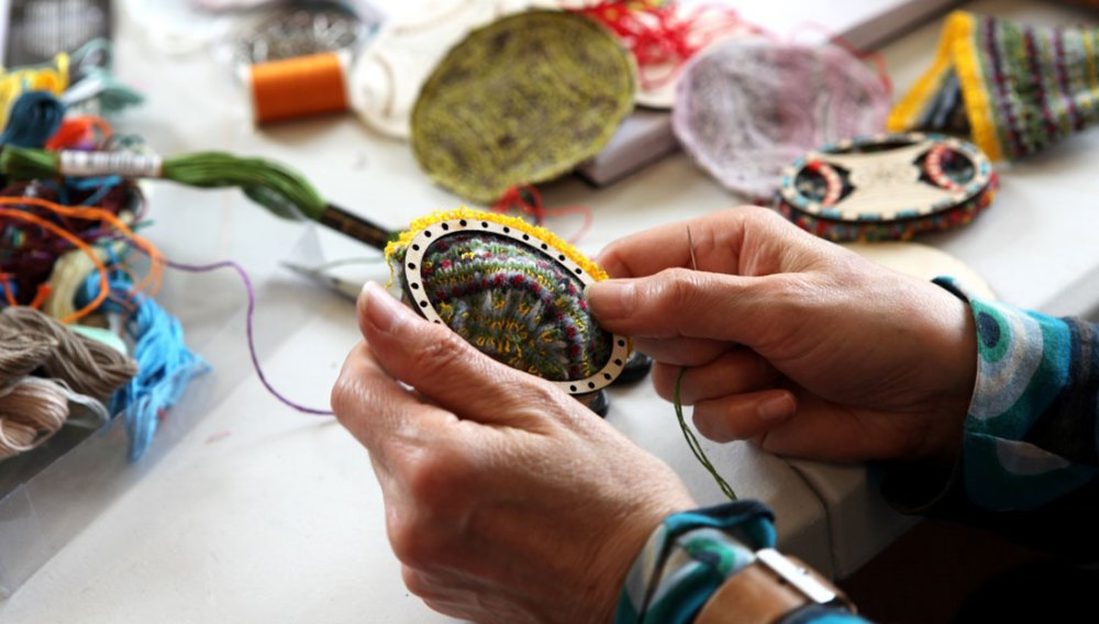 A pair of hands intricately embroider around and inside a wooden hoop.