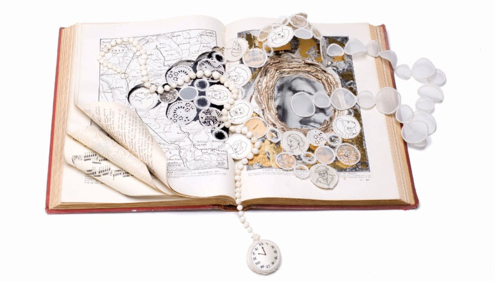 An open book displays various jewellery pieces made with textile.