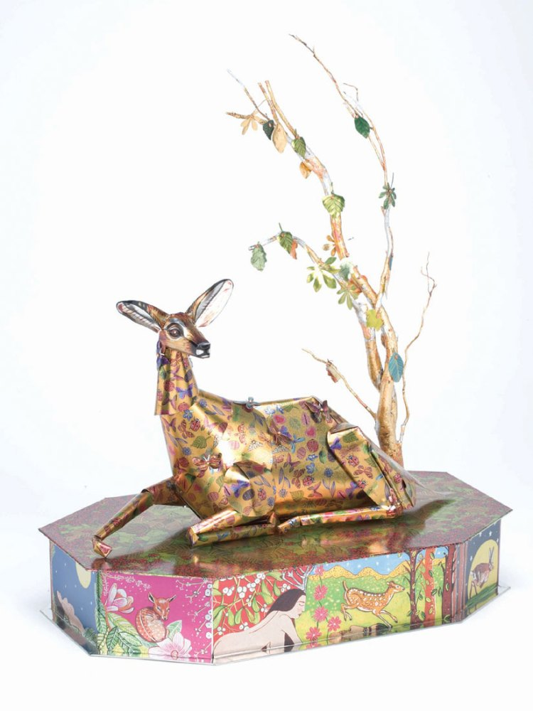 A metal deer sits on top of a metal plinth and underneath a metal tree with various deer imagery and colours printed on to it.