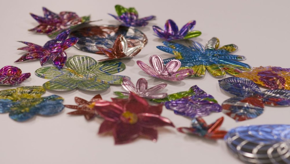 Various flowers made of sheet metal with different colours and textures applied to them.