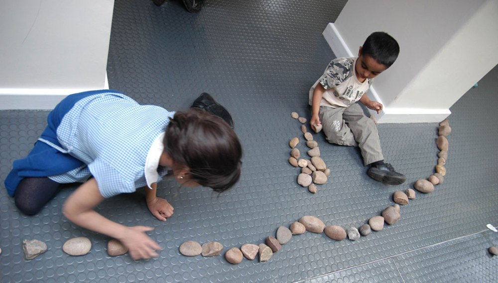 Two children lay out small rocks and pebbles in a curved form.