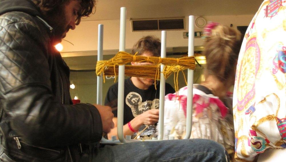 A man binds yellow thread between the legs of a chair.