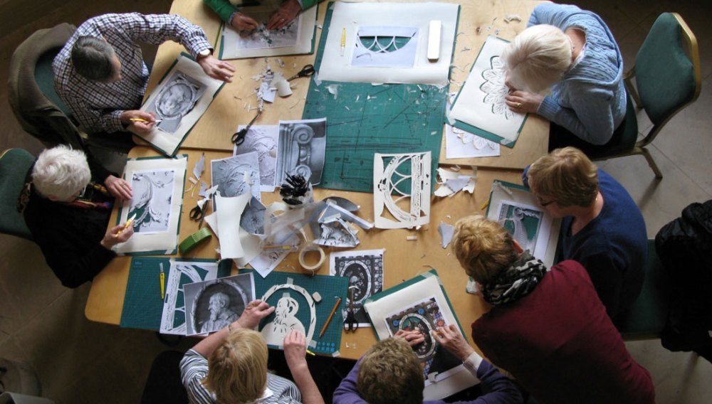 A group of people sit around a table cutting out stencils from paper.