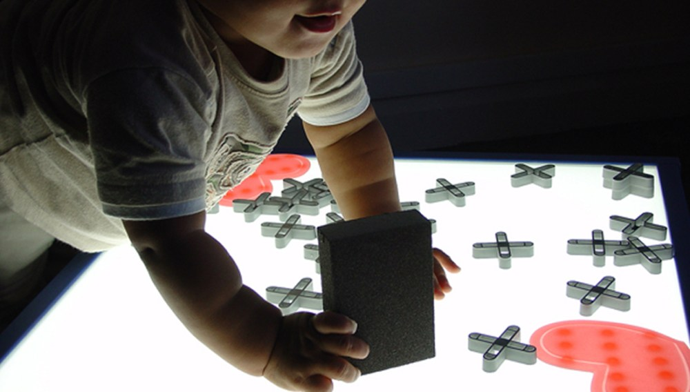 A baby leans over a lightbox, investigating plastic shapes places on top.