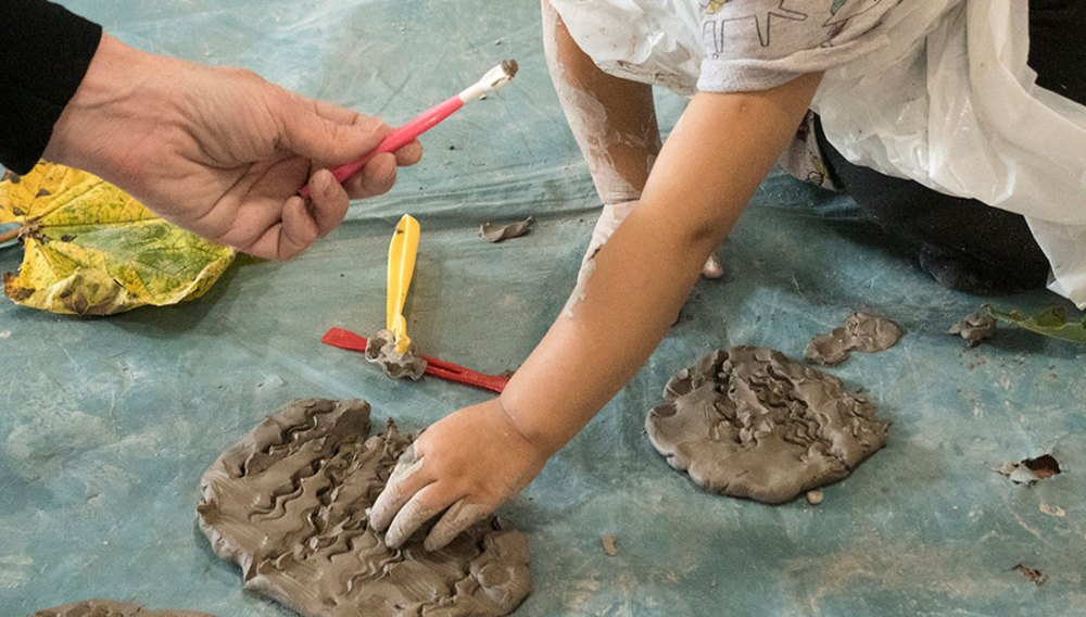 a young hand pushes into wet clay.