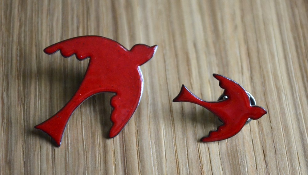 two red enameled bird brooches. simple in design.