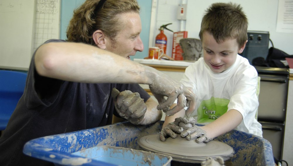 An artist helps a young boy throw a pot on the potters wheel.