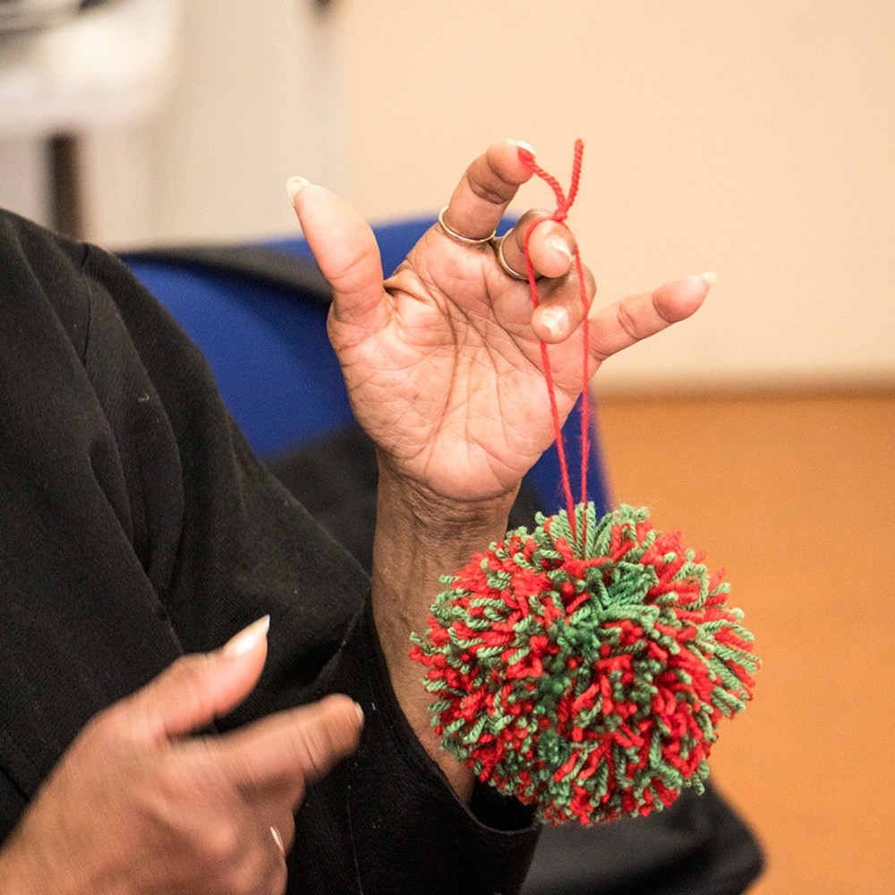 An older woman's hand holds a bright pom pom.