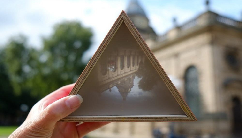 A small hand held camera obscura shows an image of the cathedral.