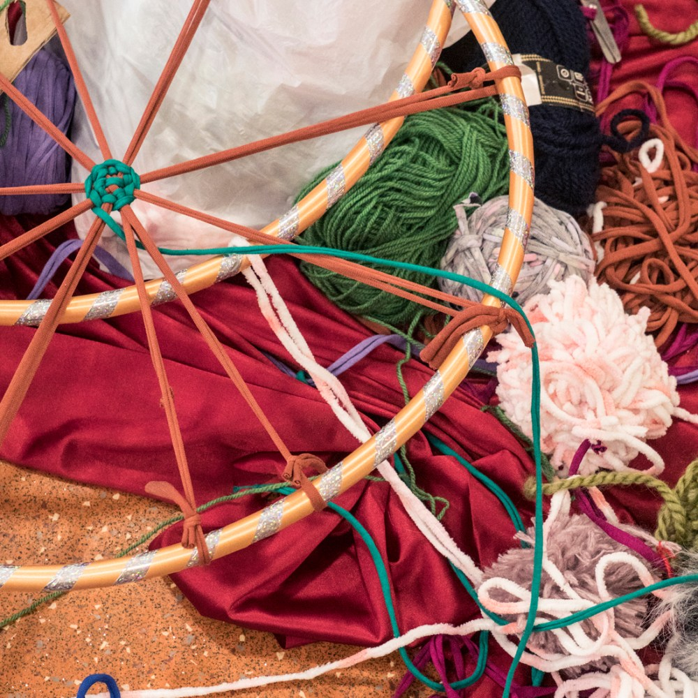 A tangle of coloured wool, hoops, material and tshirt yarn.