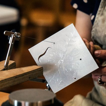 A piercing saw cuts a shape from a silver square.