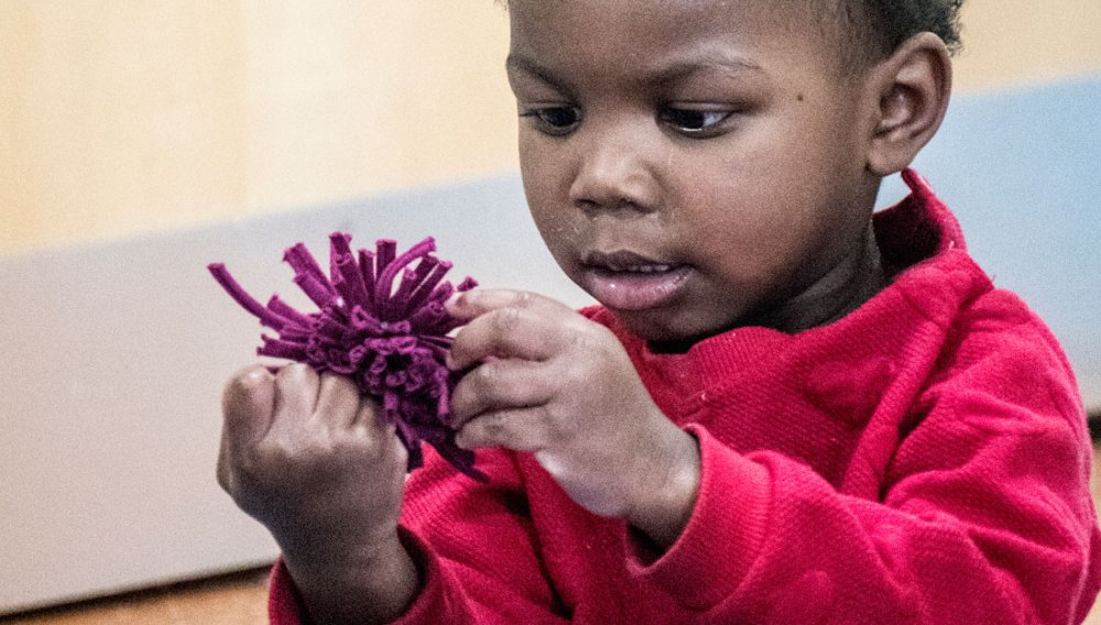 A child interacts with a fabric flower.