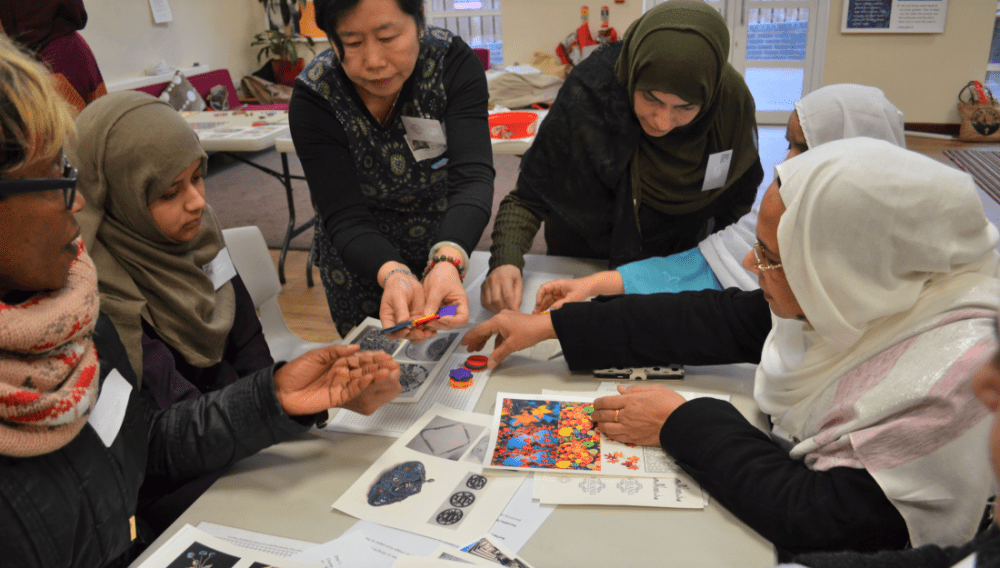 A member of Shelanu helps the group pick the colour and shape of their brooches.