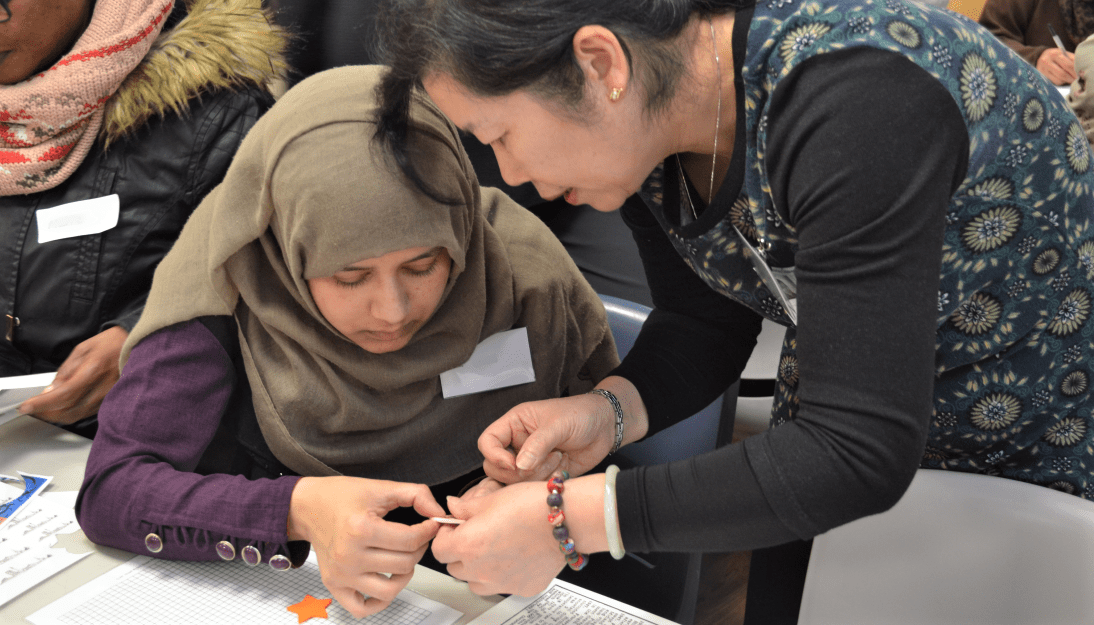 A member of Shelanu helps a lady to make her brooch