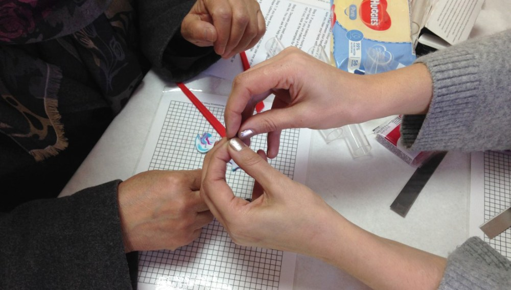 Member of Shelanu helps a member of the public make a bead
