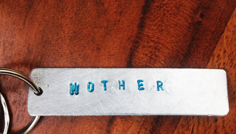 Aluminium keyring with the word mother stamped into it in blue.