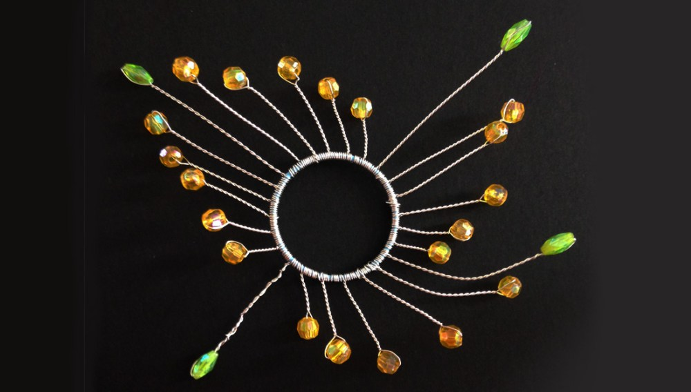 A circle shape made from jewels and wire.