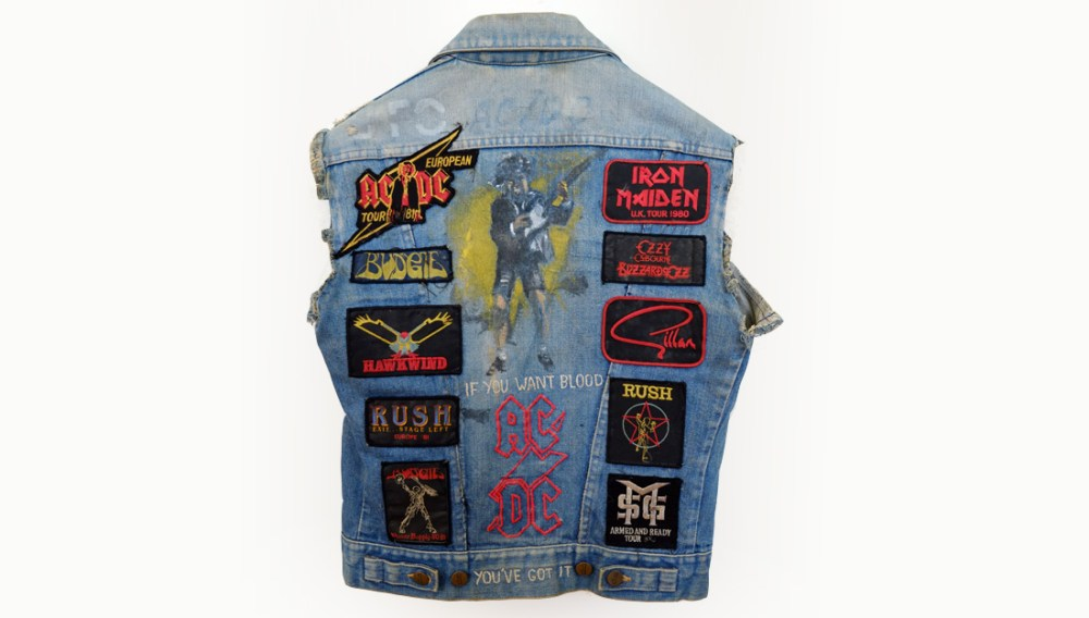 a well worn denim jacket with patches from heavy metal gigs.
