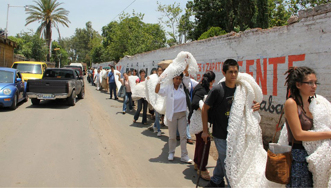 A very long line of people walk along a road carrying a very long knitted white piece of fabric on their shoulders.